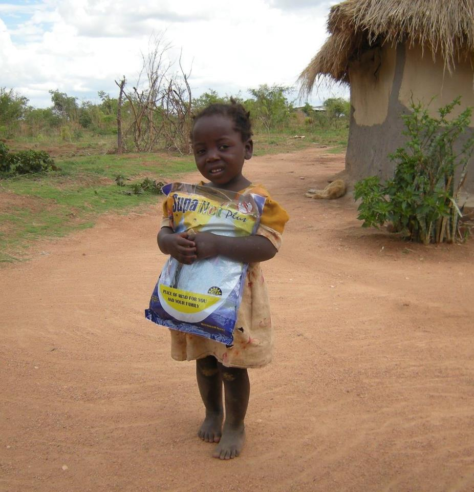A young girl from Makumba Village with her new mosquito net.