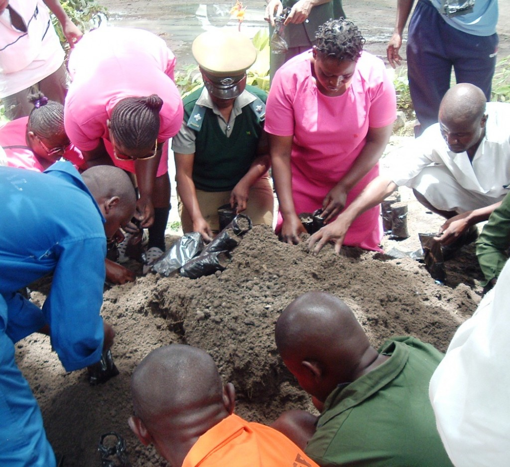 Prison staff and men and women prisoners working together fill grow pots for new trees